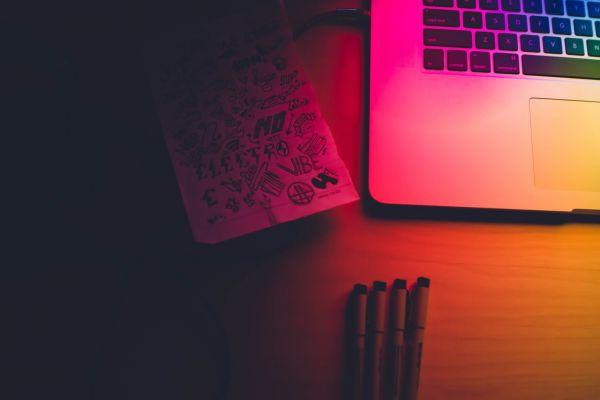Scrivania con Macbook, 4 penne e un foglio