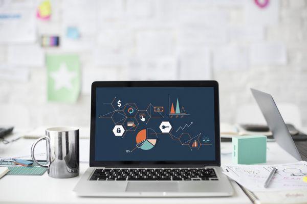 Scrivania con Macbook e grafici